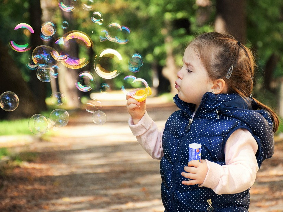 Happy kid blowing bubbles