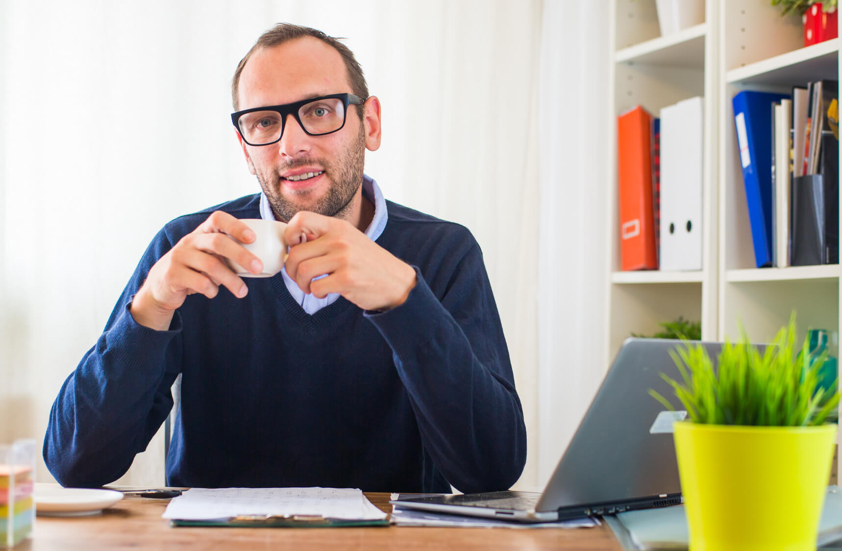 Man sitting at his desk with a cup of coffee