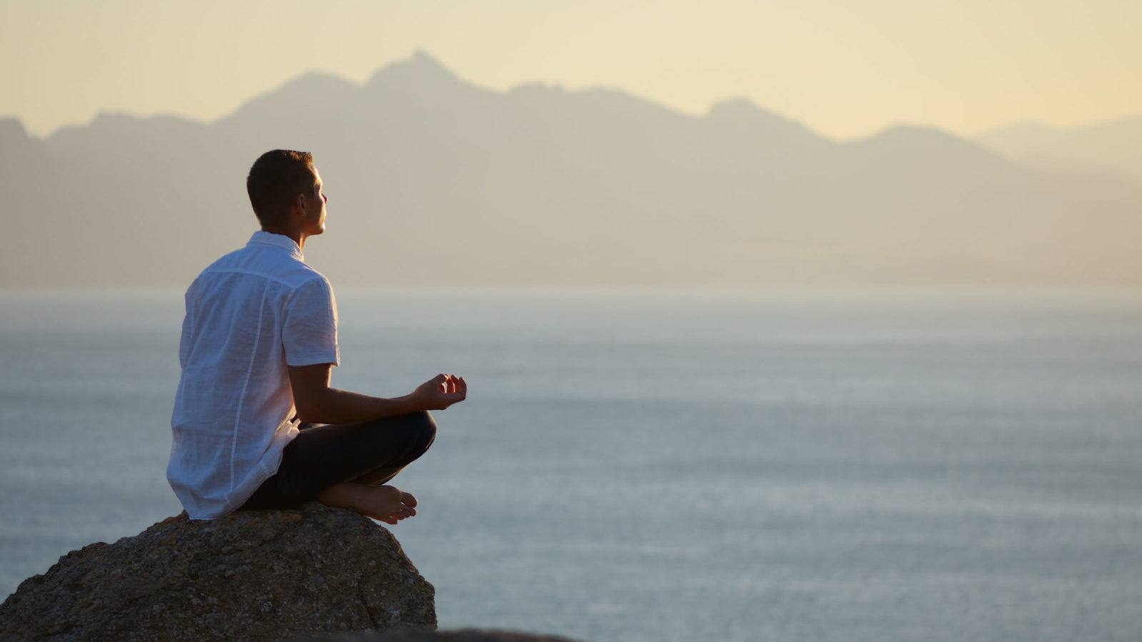 Guy sitting on a rock in the lotus position meditating