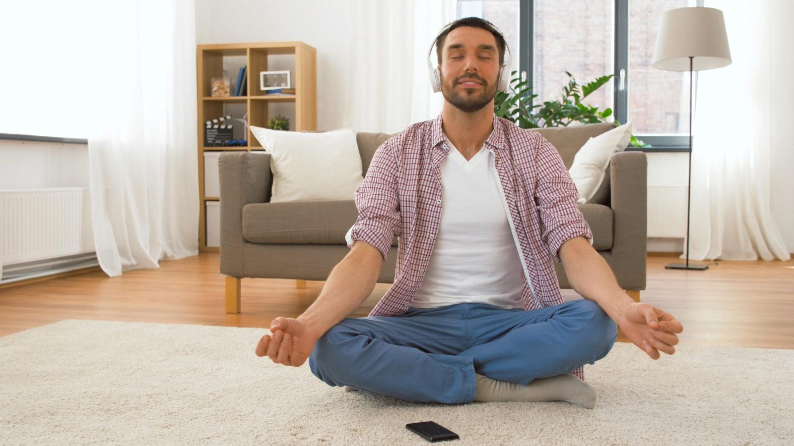 Man in headphones meditating in lotus pose at home