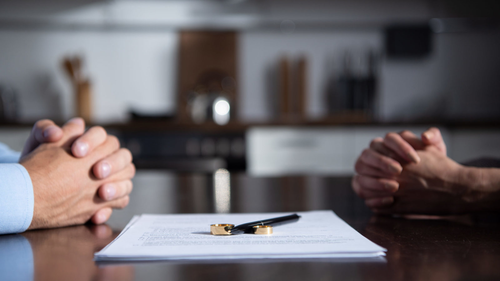 Partial view of couple sitting at table with clenched hands near divorce documents
