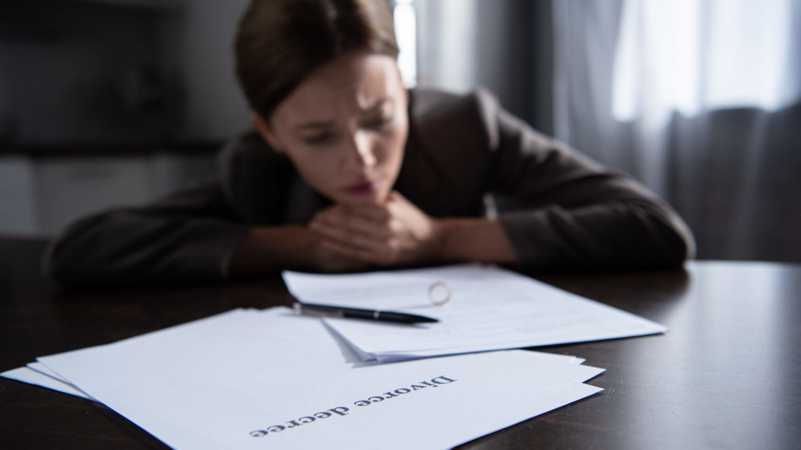 sad woman at table with divorce documents